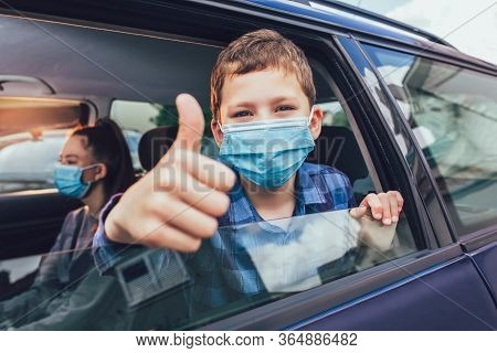 Kids Wearing Anti Virus Masks And Using Digital Tablets In The Car. Kids Are Travelling In Car Durin