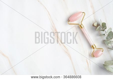 Rose Quartz Face Roller And Eucalyptus Leaf On Marble Background, Top View. Face Massage Tool, Beaut
