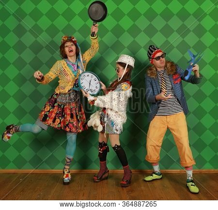 Turretless Freak Family Dressed In Color Unthinkable Clothes Pose In The Studio On A Green Backgroun