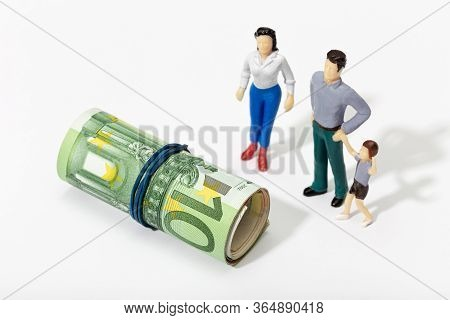 Human Representation Of A Family Looking At A Roll Of Money. Finance, Investment Or Savings Concept