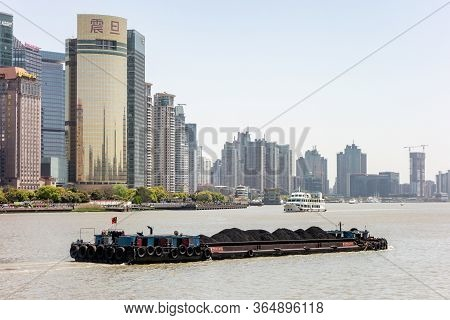 Shanghai, China - April 13, 2017: The Huangpu River In Shanghai, China With A Cargo Ship Transfering