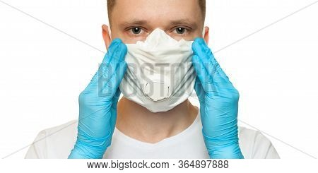 Young Surgeon Doctor In Latex Protective Gloves Puts On White Protection Mask On White Background. M