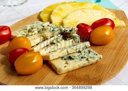 Wooden Plate With Blue Cheese Dorblue, Red And Yellow Cherry Tomatoes And Slices Of Pineapple.