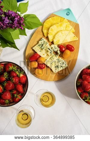 Top View Of Cheese Plate With Dorblue, Pineapple Slices And Cherry Tomatoes Serving With Bowl Of Fre