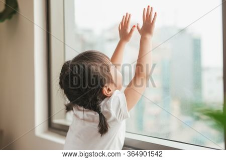 A Lovely Kid Girl Sitting And Looking Outside Trough The Window