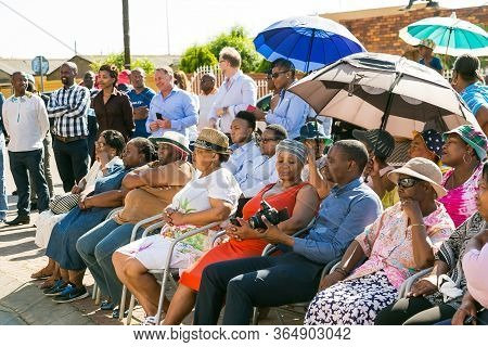 Group Of African People Sitting Together Outside Local Supermarket
