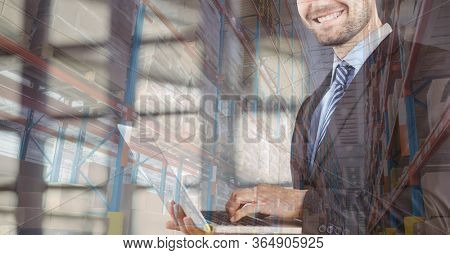 Mid section of a Caucasian man using laptop computer at home shopping on line over warehouse with shelves full of cardboard parcel boxes in the background. Online shopping ecommerce social distancing