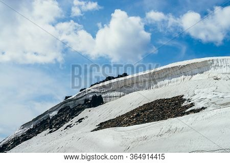 Wonderful View To Small Glacier On Stony Hill Under Blue Sky With Clouds. Beautiful Alpine Landscape