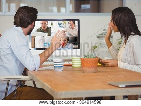 Couple waving during a video call with their friends and family on computer self isolating at home with coronavirus Covid 19 spreading. Public health social distancing and self isolation in quarantine