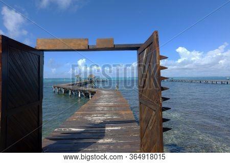 Wooden Pier Extending Over The Caribbean Sea. Open Doors Overlooking The Caribbean Ocean