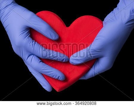 Doctor hands hold and protect a big heart on black background.