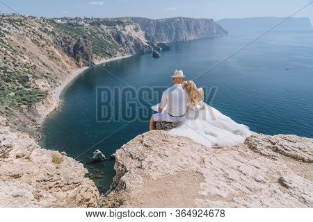 The Newlyweds Sit With Their Arms Around Each Other And Look At The Beautiful Seascape Of Fiolent. T