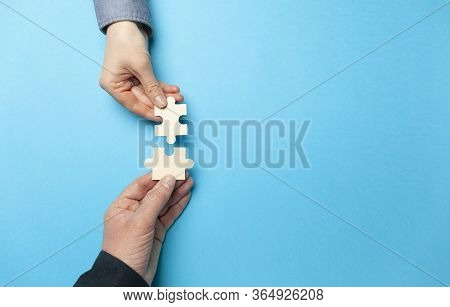 Two Hands Connect Puzzles On A Blue Background. Cooperation And Teamwork In Business. Collaboration