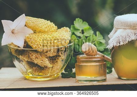Honey Jar And Flowes On Table Against Nature Background. Jar Of Organic Floral Honey And Honeycomb