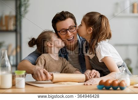 Happy loving family are preparing bakery together. Father and children daughters girls are cooking cookies and having fun in the kitchen. Homemade food and little helper.