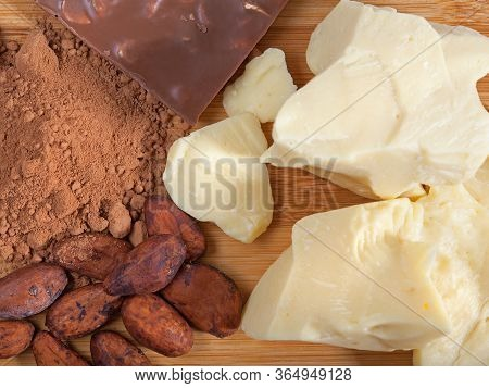 Pieces Of Natural Cocoa Butter, Bar Of Milk Chocolate, Cocoa Powder And Cocoa Beans On Wooden Cuttin
