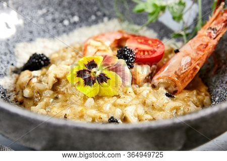 Risotto with seafood in gray bowl . Italian rice porridge with shrimps close up. Traditional food with violet flowers, black caviar, tomato and greenery decoration. Served delicatessen