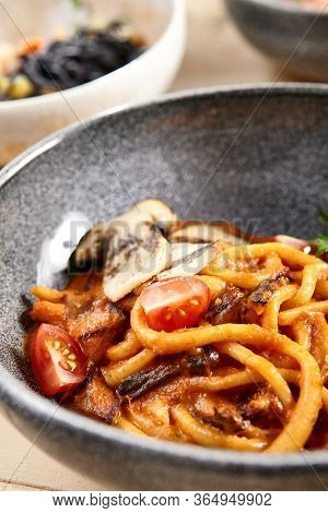 Pichi with mushrooms and creamy tomato allione in gray bowl. Pasta with vegetables close up. Delicatessen, served restaurant meal, tasty noodles with tomato and greenery leaves decorations