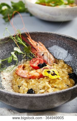 Risotto with seafood in gray bowl  closeup. Italian rice porridge with shrimps close up. Traditional food with violet flowers, black caviar, tomato and greenery decoration. Served delicatessen