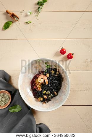 Black spaghetti with shrimp and zucchini in beige bowl. Pasta with cuttlefish ink close up. Delicious delicatessen, served restaurant meal, tasty noodles with seafood and vegetables