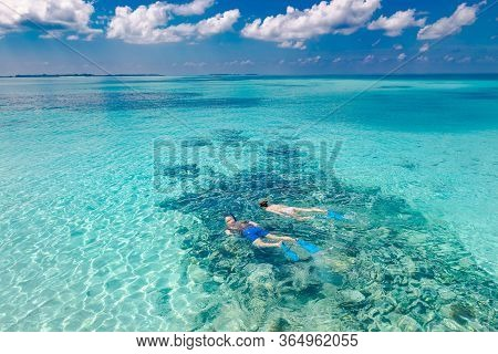 Caucasian Couple Of Tourists Snorkel In Crystal Turquoise Water Near Maldives Island. Exotic Summer
