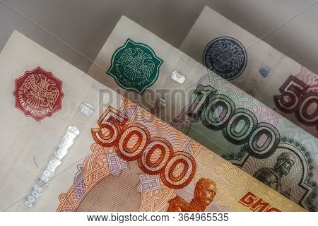 Russian Banknotes Of 5000, 1000, And 500 Rubles Are Hanging Over A Gray Background. Dark, Gloomy Ill