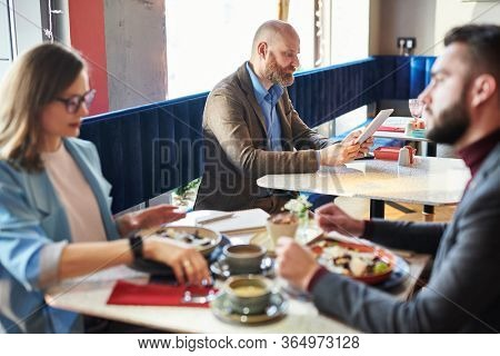 Serious bald man sitting at table and using tablet connected to wifi while working in modern cafe