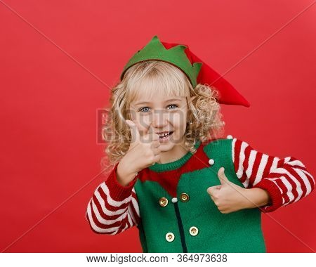 Merry Christmas Child Showing Thumb Up Like In Santa Elf Helper Costume On Bright Red Vivid Color Ba
