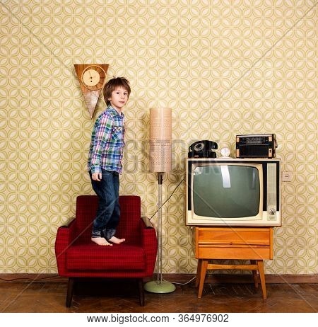 Vintage art portrait of liitle boy jumping on armchair in room with interior from 70s 20th century, retro stylization, image toned. Child at home with old tv set