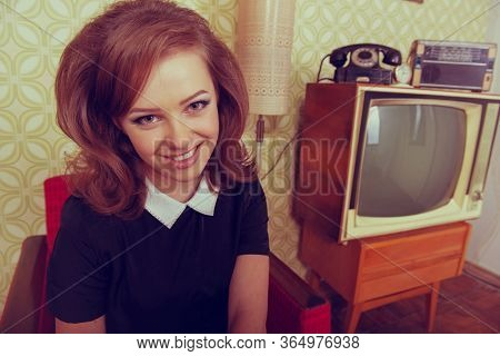 Young smiling ecstatic woman looking at camera, smiling in room with vintage wallpaper and interior, retro stylization 60-70s. Furniture, tv set and another technique of the mid 20th century