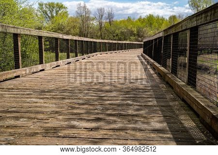 Low Angle View Of A Pedestrain Footbridge In Elm Creek Park Reserve Along The Trails On A Spring Day