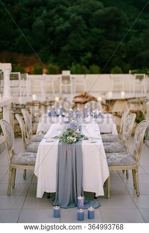 Wedding Dinner Table Reception. A White T-shaped Table With A Grey Tablecloth And Lots Of Blue Candl