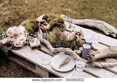 Wedding Dinner Table Reception. An Impromptu Table For Two Of The Construction Pallet On Grey Grass