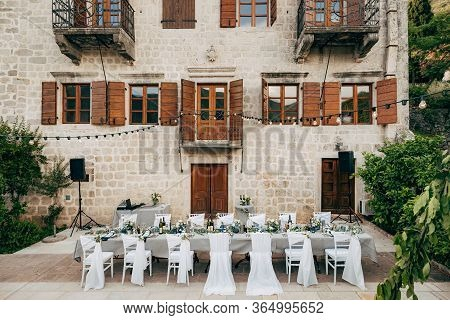 Wedding Dinner Table Reception. Grey Long Rectangular Table And Fourteen Chairs Outside The Old Vill