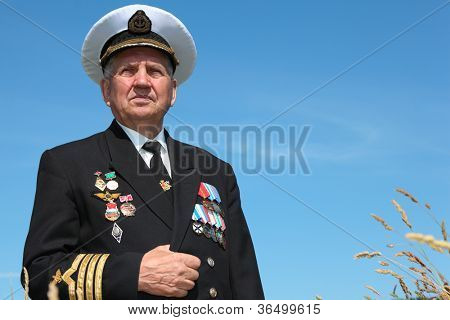 Grandfather in form, cap, ordens, medals pose background sky poster