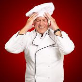 Portrait Of Chef With Painfully Head On Red Background poster