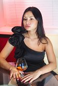 beautiful woman in black dress on sofa with glass of brandy poster