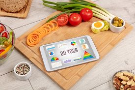 Organic food and tablet pc showing DO YOGA inscription, healthy nutrition composition