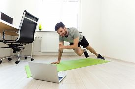 Man Doing Exercises At Home With Online Tutorial. Man Watching Laptop Doing Sports. Video Call Pract