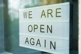 Lightbox With As Sign We Are Open Again Behind A Glass Door Of The Cafe. Were Open Again After Quara