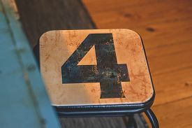The Number 4 On A Small Chair In A Room With Wooden Floors In Blue And Warm Colors
