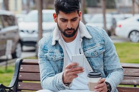 Bearded Stylish Indian Man Outdoors Using App In His Smartphone.