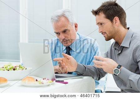 Two Business People Working On Laptop at Lunch In Restaurant