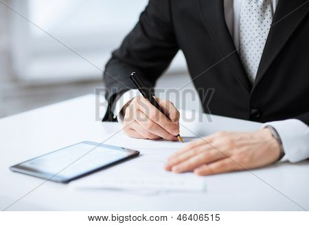 close up of man with tablet pc signing paper poster