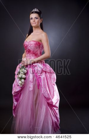 Portrait of a happy young bride posing in a pink wedding dress holding bouqet of white flowers. poster