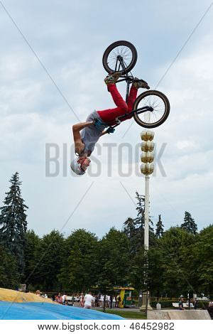 MOSCOW - AUG 4: Guy does somersaults on bike at All-Russian Exhibition Centre during holiday dedicated to 73d birthday of country main exhibition, August 4, 2012, Moscow, Russia.