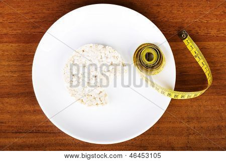 Diet concept. Biten rice cake on plate next to measuring tape.