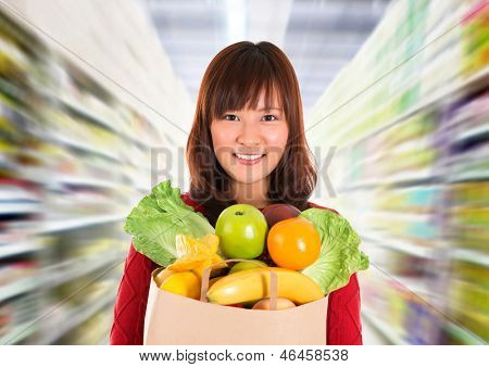 Asian grocery shopping. Smiling young woman holding paper shopping bag full of groceries in a grocery store/supermarket .