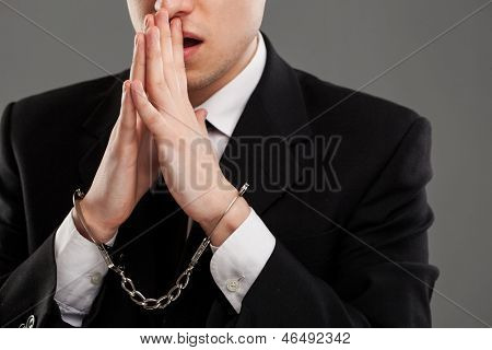 Businessman in suit with closed manacles on his hands