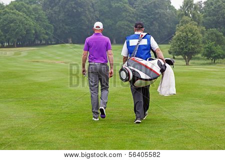 Golfer and caddy walking towards a ball on a par 4 fairway.